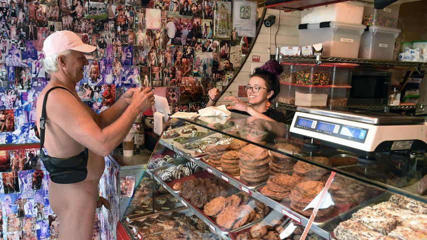 Ein Mann, kauft vor Beginn der Nude Love Parade in San Francisco, Kalifornien, einenKeks bei Hot Cookie.