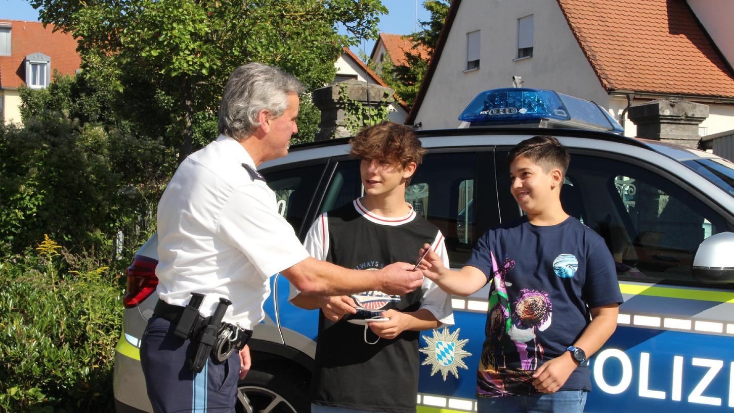 Der stellvertretende Dienststellenleiter Marco Lenz zeigt Fabio Klinger (13, rechts) und Luca Scoccimarro (15) die Polizeiinspektion Gunzenhausen. Im Hof überreichte er ihnen zudem einen Gutschein für einen Onlineshop.