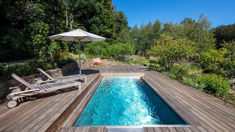 Multifunktionale Abdeckung: Dank eines verschließbaren Holzdecks kann aus einem Pool an kühlen Tagen auch eine Terrasse werden.