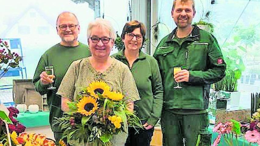 """Ihr 40-jähriges Betriebsjubiläum in der Gärtnerei Roßbacher hat Lisa Manhard (2.v.li.), geborene Karl, gefeiert. Am 1. September 1981 war die damals 15-Jährige aus der Nachbarsiedlung angetreten, um den Beruf der Floristin zu lernen. Sie besuchte drei Jahre die Berufsschule für Floristik in Kulmbach. Im Juli 1984 meisterte Manhard die Abschlussprüfung mit Bravour. Seither erlebte sie und setzte viele Meilensteine und Veränderungen in der Gärtnerei mit um. Inzwischen arbeitet sie mit der dritten Generation des Familienbetriebes zusammen. Für die Kunden sei Manhard mit ihrer freundlichen Art nicht wegzudenken, weil sie viele Balkone und Blumenkästen fast persönlich kenne und Sonderwünsche blind erfülle, lobt ihr Arbeitgeber. Er dankte für ihr tägliches Engagement und die lange Treue und wünschte: """"Liebe Lisa, bleib wie du bist und uns mit deinem sonnigen Gemüt noch lange erhalten."""""""