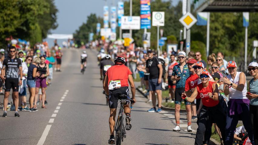 05.09.2021, Bayern, Eckersmühlen: Zuschauer und Helfer unterstützen die Triathleten auf der Strecke während der Radetappe beim Datev Challenge Roth. Bei der 19. Auflage des Triathlons müssen die Teilnehmer 3,8 km schwimmen, 170 km mit dem Rad absolvieren und 42,2 km laufen. Foto: Daniel Karmann/dpa +++ dpa-Bildfunk +++