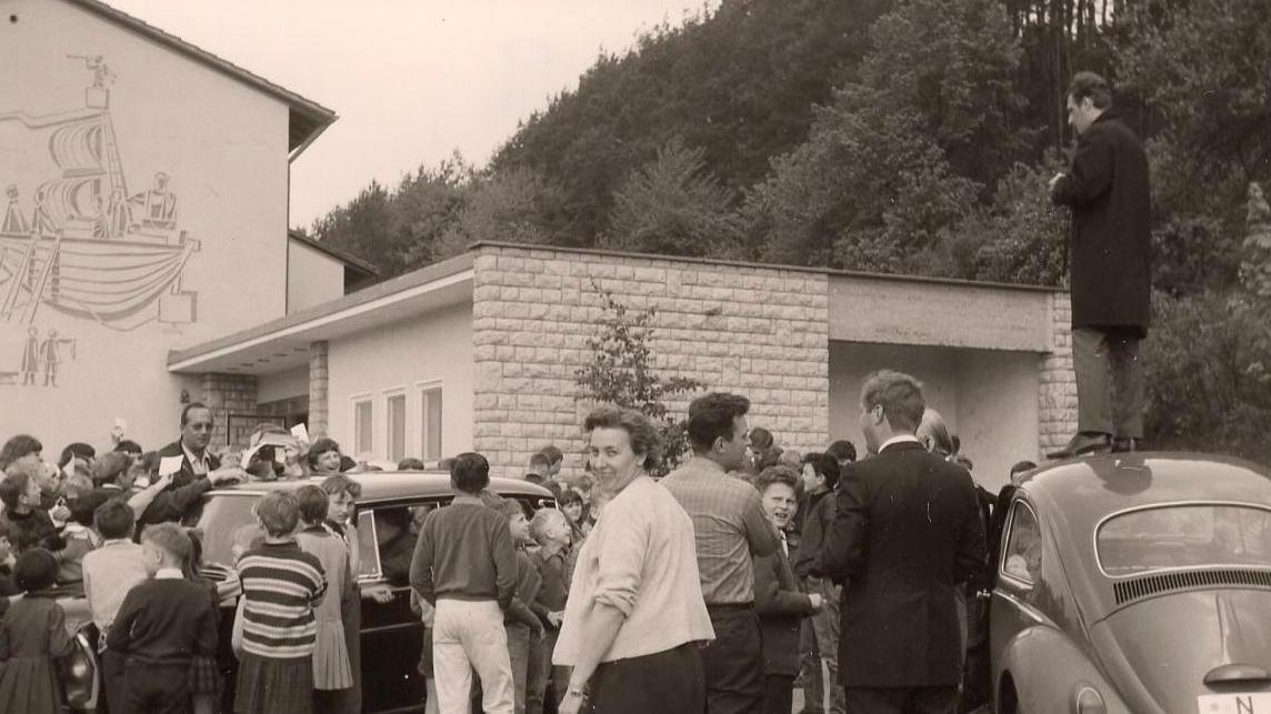 NN-Reporter Rudolf Kroack steht auf dem Autodach und fotografiert Max Merkel bei seiner Autogrammstunde in Unterleinleiter.