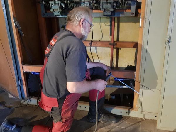 Ein früherer Schaltschrank in der Maschinenhalle des Bergwerks Maffei wird für die Installation eines Monitors umgebaut. Im Bild Hans Warta.