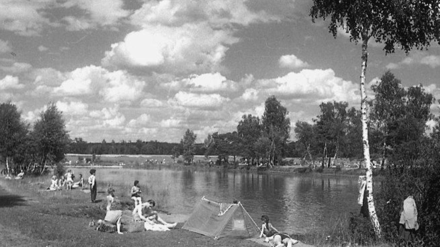 Still ruht der See: Naturbelassene Idylle dominiert die Szene, hier und dort haben sich Familien am Ufer niedergelassen – doch wo könnte das sein? Und in welchem Sommer ist die Aufnahme entstanden?