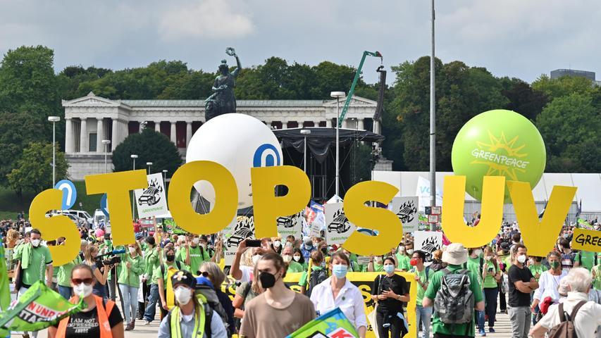13.03.2020, Bayern, München: Demonstrationsteilnehmer ziehen mit Plakaten und gelben Buchstaben, die den Schriftzug «Stop SUV» formen, in Richtung der Innenstadt. Unter dem Motto «#aussteigen» finden eine Demonstration und eine Fahrradsternfahrt gegen die Internationale Automobil Ausstellung (IAA) statt. Foto: Felix Kästle/dpa +++ dpa-Bildfunk +++
