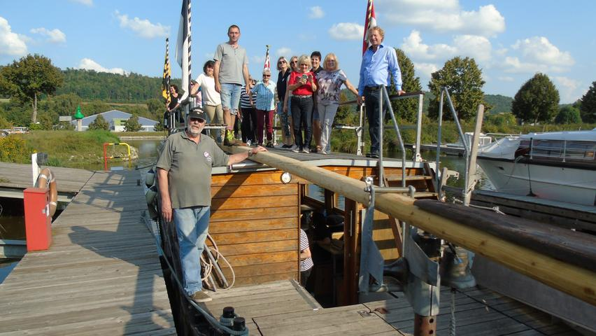 Links steht Kapitän Ulrich Burst und oben auf dem Schiff die Vorsitzenden des Jachtclub Berching, Dominik Scholl und Ralf Vaters.