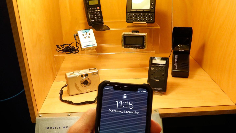 Ein Smartphone ersetzt die vielen Geräte, die im Hintergrund zu sehen sind.