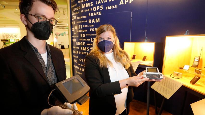 Christian Bihn und Museums-Direktorin Annabelle Hornung zeigen einen Pager von T-Mobile und ein