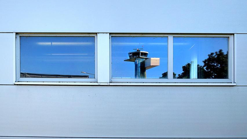 Das Fenster zur Welt: Der Tower des Nürnberger Flughafens spiegelt sich im Fenster eines Nebengebäudes.