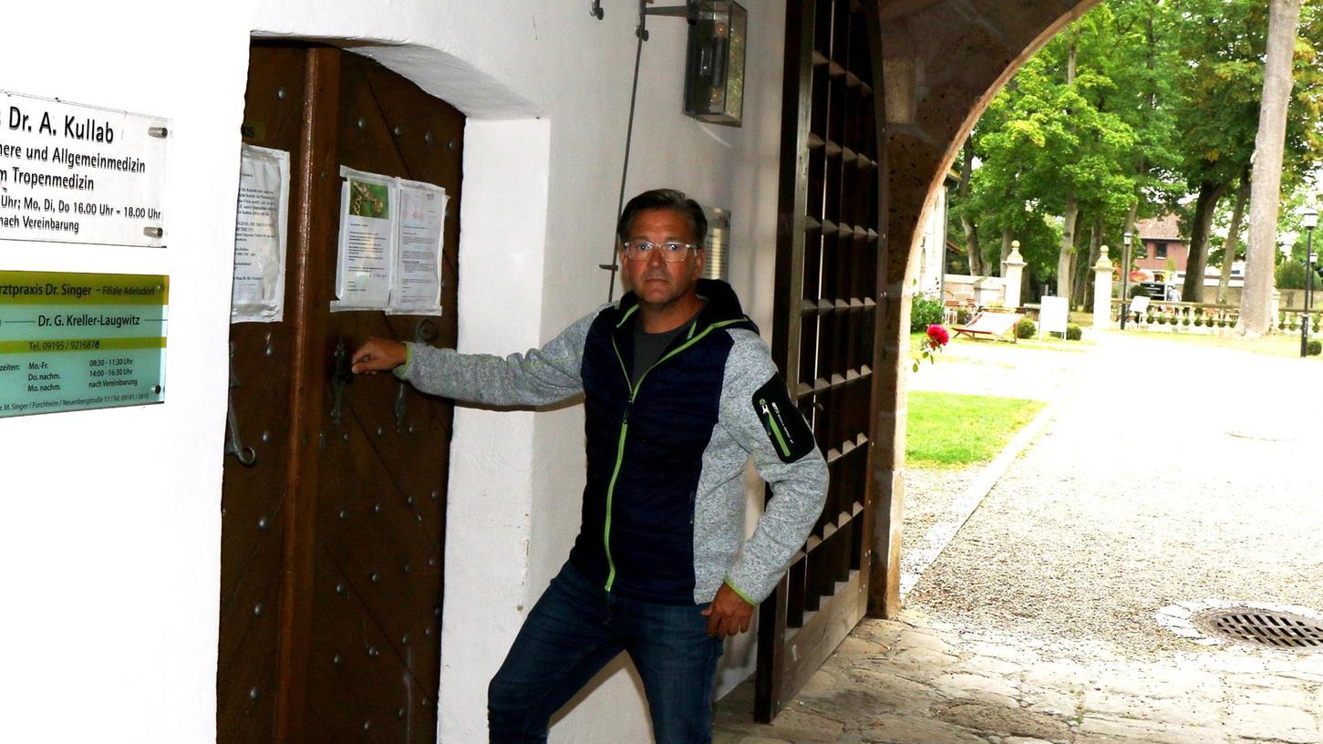 Bürgermeister Karsten Fischkal vor der dicken Holztür an der Praxis im Schloss.