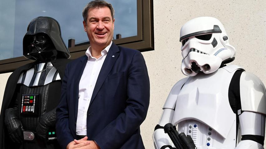 Markus Söder (Mitte), selbst Star-Wars-Fan, ließ sich mit Darth Vader (links) und einem Sturmtruppler (rechts) abbilden.