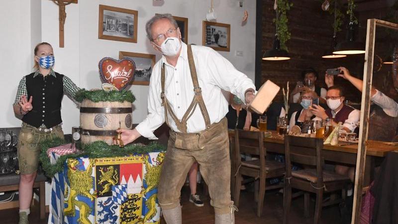 Der ehemalige Münchner Oberbürgermeister Christian Ude zapft mit Mundschutz ein Bierfass an.