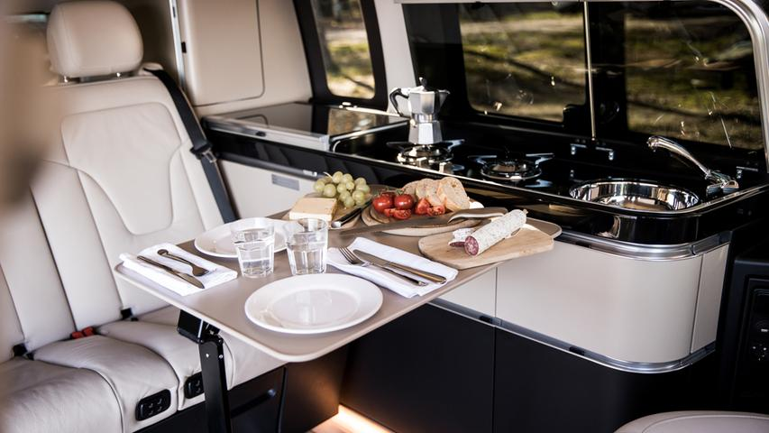 Edel eingerichtet: Wohn- und Kochbereich mit Boden in heller Yachtoptik, Ledermobiliar und schicker Küchenzeile.