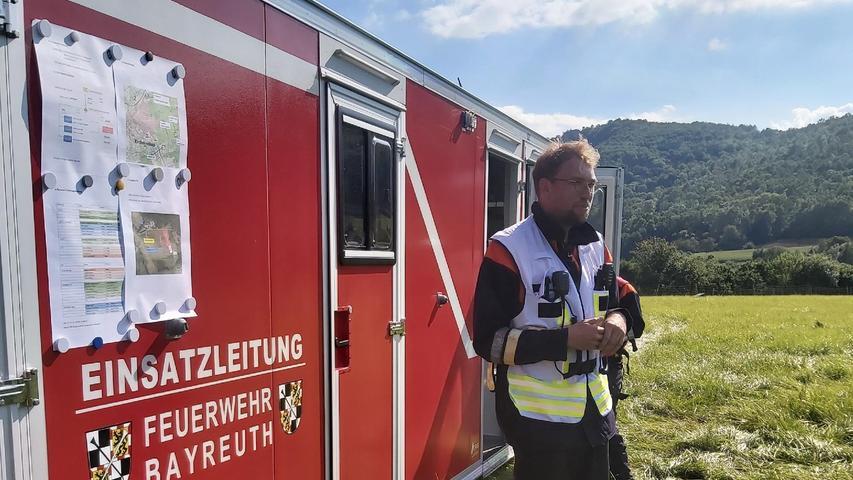 """Hier erklärt auch der Leiter der Flughelfergruppe Bayreuth, Lucas Lauterbach, deren Vorgehen. """"In der ersten Phase bauen wir den Landeplatz auf und fliegen Personal an den Berg hoch. In der zweiten Phase wird Material wie Schläuche durch die Luft an den Einsatzort gebracht. In der dritten Phase werden die Wasserbehälter per Schlauchbefüllung durch die Einsatzfahrzeuge der Feuerwehr Forchheim befüllt."""""""