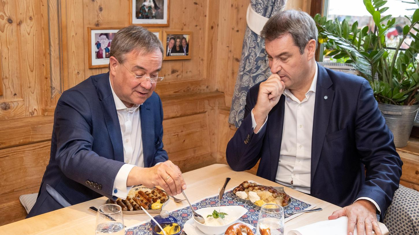 Bayern, Nürnberg: Markus Söder (r), CSU-Parteivorsitzender und Ministerpräsident von Bayern, und Armin Laschet, Unions-Kanzlerkandidaten, CDU-Vorsitzender und Ministerpräsident von Nordrhein-Westfalen, essen zusammen in einem Bratwurst-Restaurant Nürnberger Würstchen.