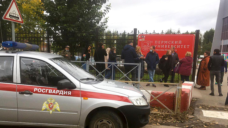 Menschen stehen hinter dem Zaun in der Nähe der Staatlichen Universität Perm.