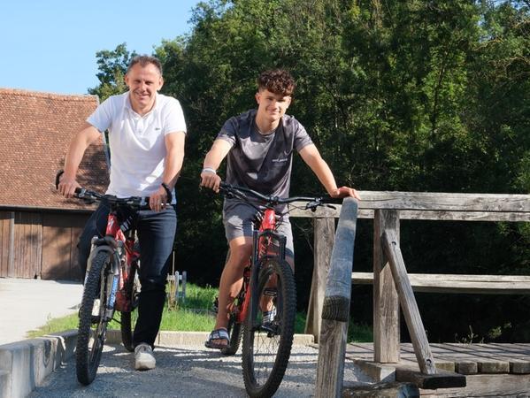 Vater Gerold und Sohn Luca Wolfarth (hier an der Tauberbrücke in Archshofen) verbindet auch der Spaß am Bergabfahrt-Radeln.