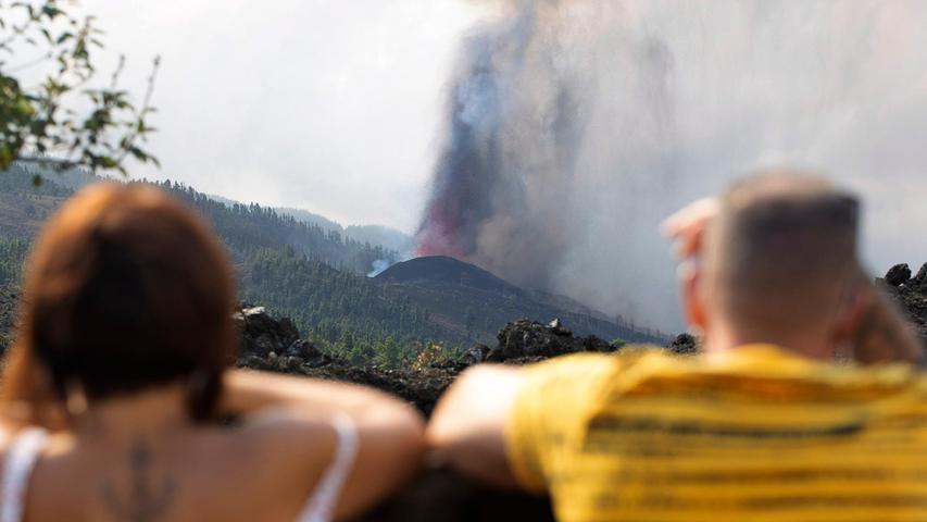 Menschen beobachten, wie Lava aus einem Vulkanausbruch in der Nähe von El Paso auf der kanarischen Insel La Palma fließt. Der Chef der Regionalregierung der Inseln sagte am Montag, er erwarte keine Verletzten, nachdem etwa 5000 Menschen evakuiert worden waren.