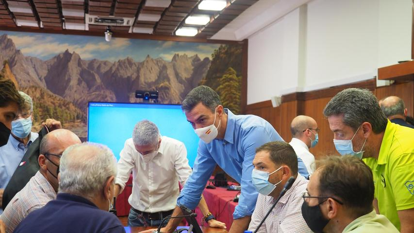 Fernando Grande-Marlaska (M-l), Innenminister von Spanien, und Pedro Sanchez (M-r), Ministerpräsident von Spanien, nehmen an einem Treffen des Notfall- und Katastrophenschutzteams während des Vulkanausbruchs auf der kanarischen Insel La Palma teil.