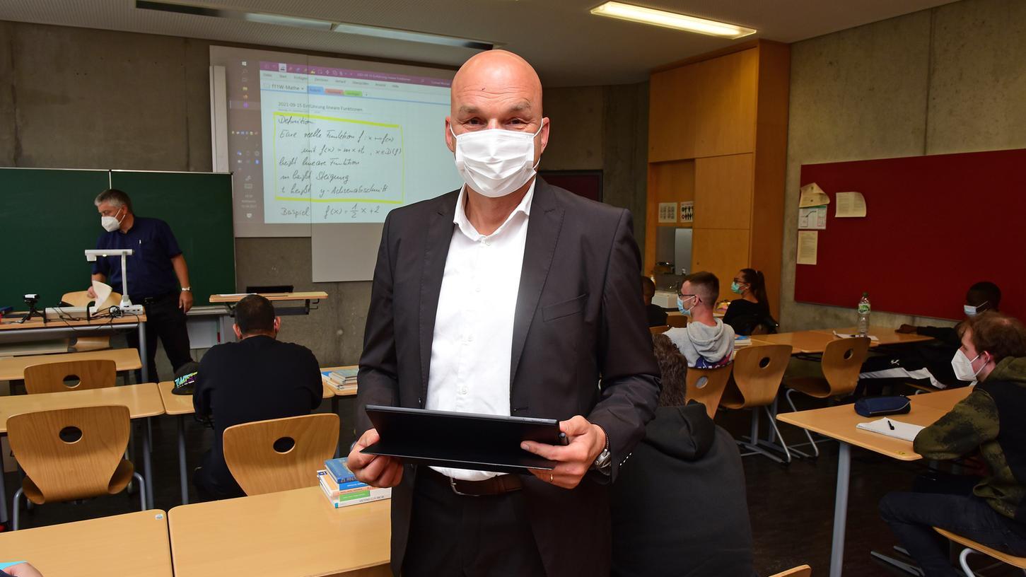 Schulleiter Thomas Schock in einem digitalen Klassenzimmer der Max-Grundig-Schule. Mit dem Tablet wird das Tafelbild erzeugt, der Beamer wirft es an die Wand.