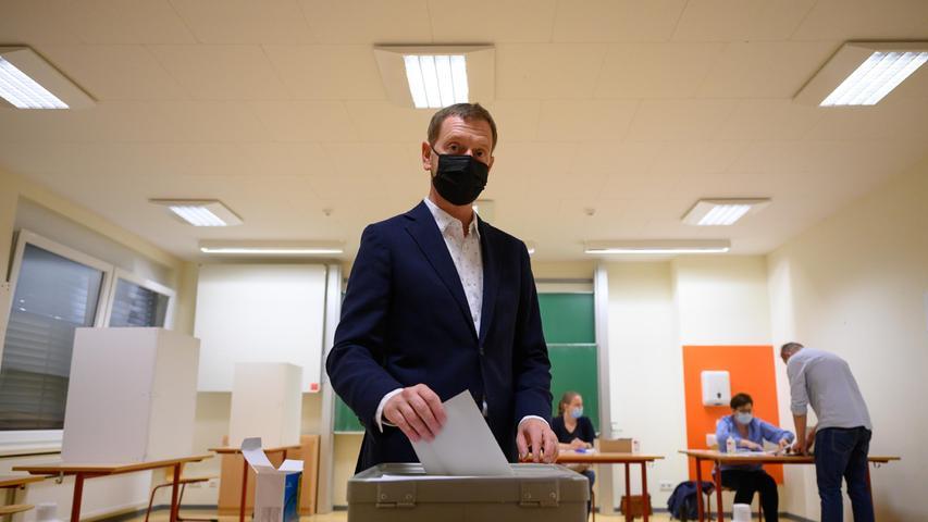 Sachsens Ministerpräsident Michael Kretschmer (CDU)wirft bei der Stimmabgabe zur Bundestagswahl im Wahllokal seinen Stimmzettel in eine Wahlurne in Dresden.