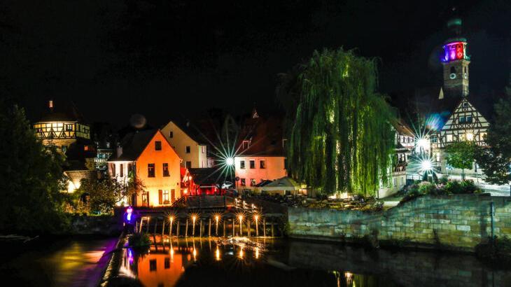 Die Reichelsche Schleif an der Wasserbrücke erstrahlt zurzeit in rotem Licht. Auch die Gebäude dahinter, wie der Judenturm, sind beleuchtet, um Tiefe zu schaffen.