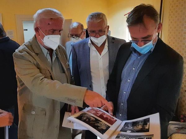 Rudolf Weber (links) kann jedes der alten Bilder im Fotobuch genau erklären und hatte aufmerksame Zuhörer.