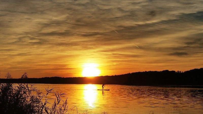 Nur keinen Sonnenstrahl verpassen: Ein Stand-up-Paddler bei Sonnenuntergang auf dem Rothsee.