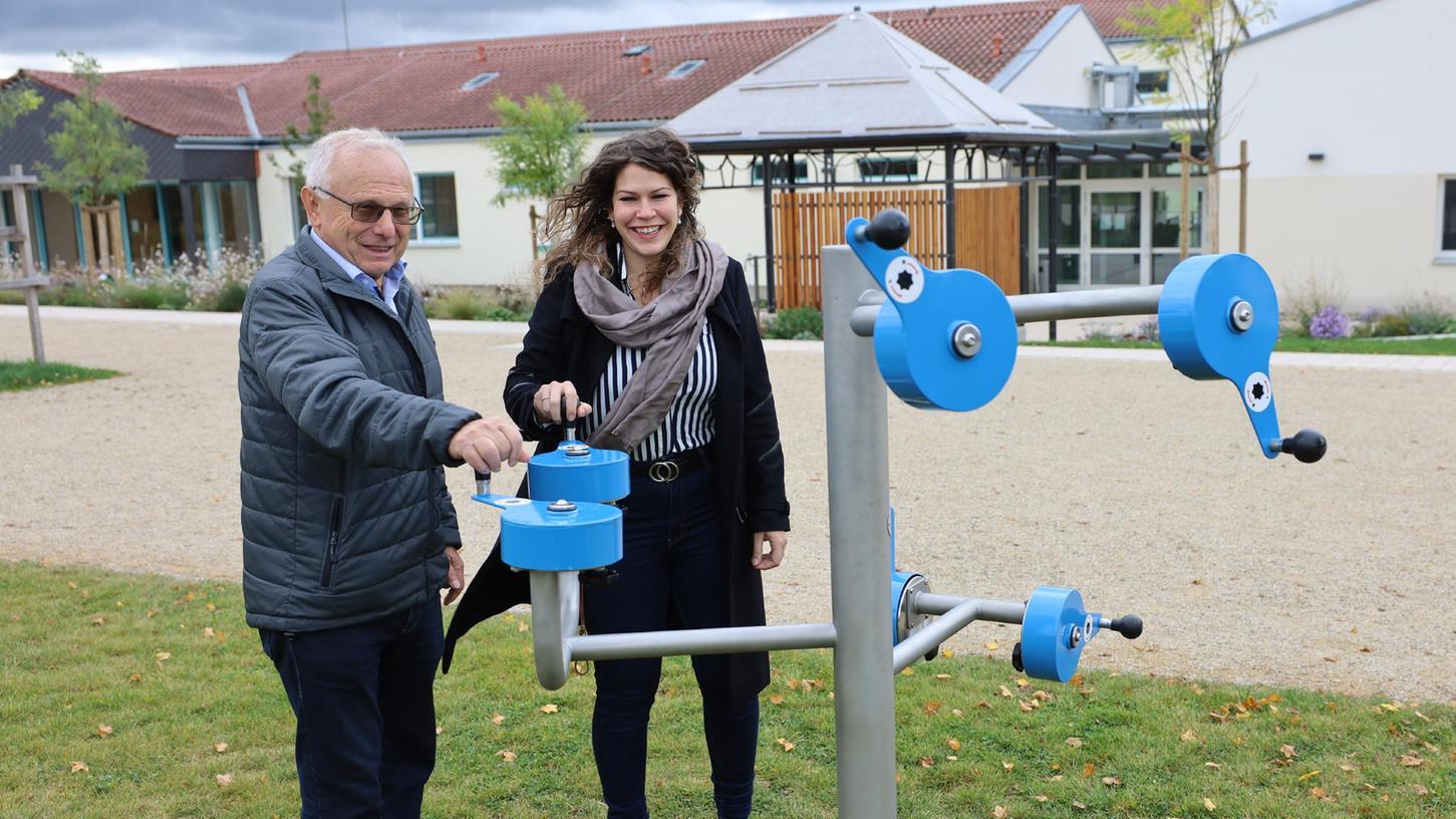 Helmut Lottes und Sofie Wedel zeigen, wie dieses Fitnessgerät auf dem Mehrgenerationenplatz funktioniert. Im Hintergrund ist das Haus der Begegnung zu sehen.