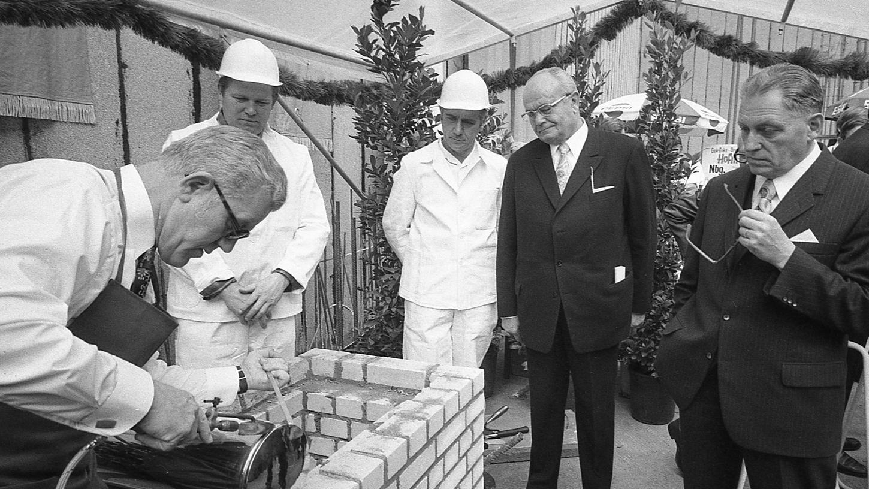 Sparkassen-Generaldirektor Max Weberpals (rechts) und Bürgermeister Franz Haas (daneben) warten darauf, daß die Kupfer-Kassette zugelötet ist.