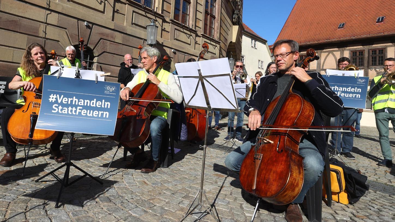 Orchestermusiker aus ganz Bayern sowie Thüringen und Baden-Württemberg musizieren während eines Flashmobs hinter Plakaten, auf denen