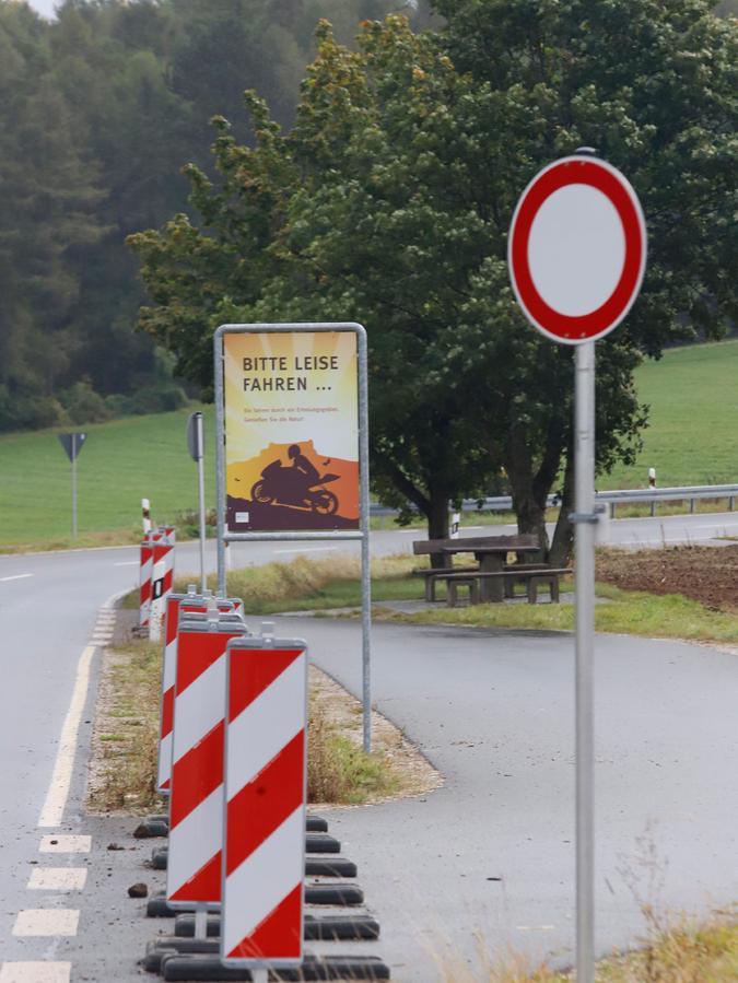 Warnbaken halten Autos vom Parken in den Parkbuchten ab. Hinweisschilder erinnern Motorradfahrer, leise zu fahren.