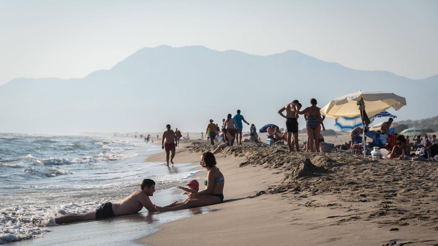 Eine Familie genießt noch im Herbst das warme Wasser amPatara-Strand beiAntalya.