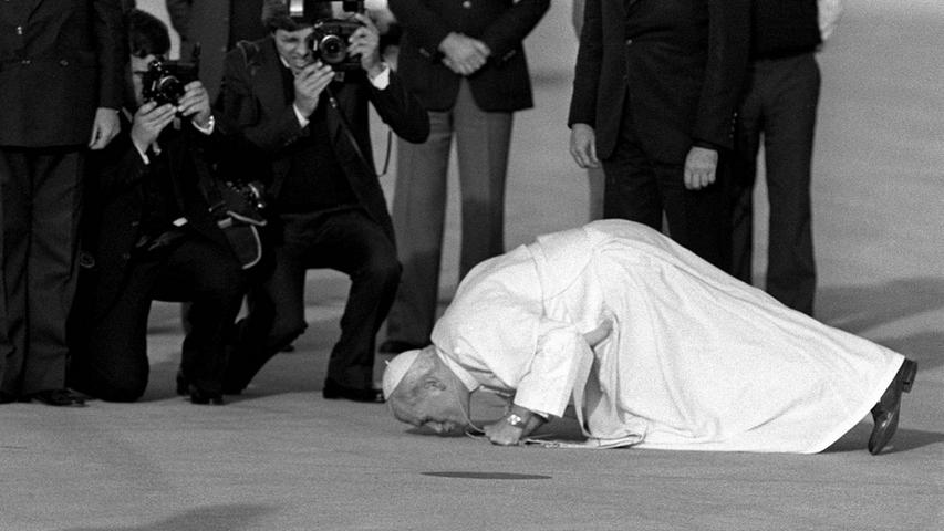 ...der Kuss von Papst Johannes Paul II. zu verstehen. Im Oktober 1982 küsst der Pontifex den Boden des Flughafens in Madrid. Jedesmal, wenn er ein Land zum ersten Mal betrat, zeigte er durch seinen Kniefall und das Küssen des Bodens seine Ehrerbietung.