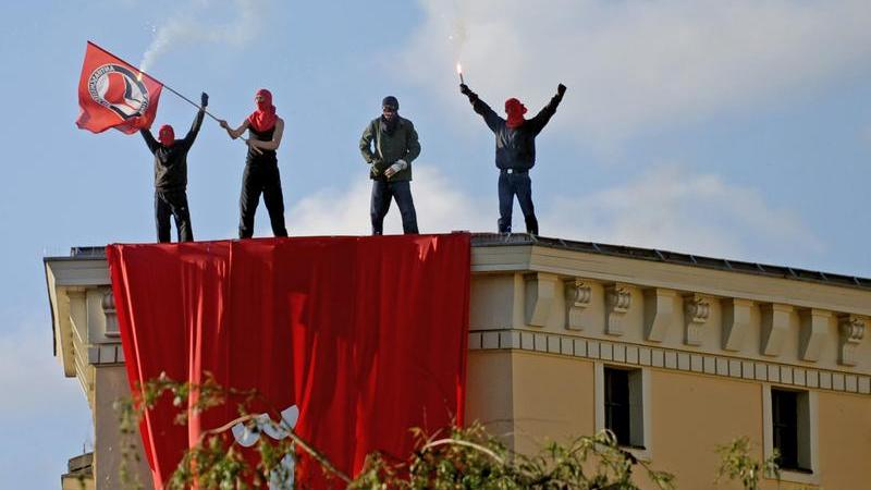 Linke Demonstranten auf einem Hausdach in Berlin-Kreuzberg.