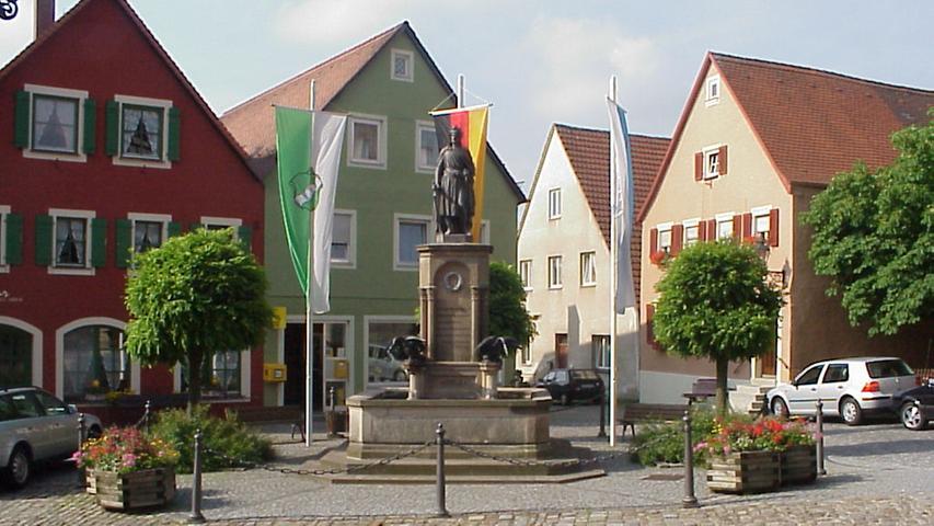 Der Marktplatz ist das lebendige Zentrum des kleinen ursprünglichen Städtchens Wolframs-Eschenbach. Seit 1917 trägt esden Namen seines großen Sohnes undberühmten Minnesängers Wolfram, der hier geboren und beerdigt wurde. Starke mittelalterliche Wehrmauern mit zwei Toren umspannen den Ort. Die Hauptstraße ist von Fachwerk gesäumt. Und dasMuseum