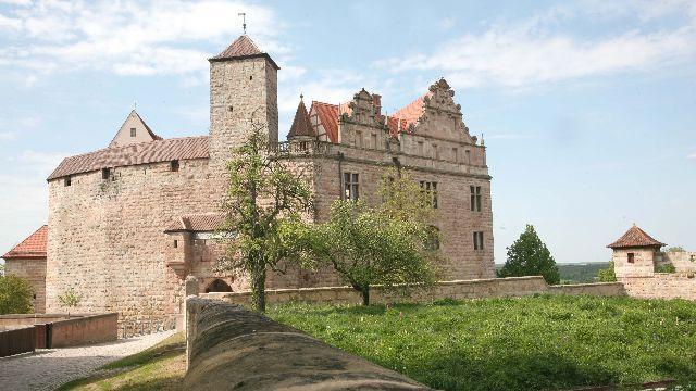 1157 wird dieBurg Cadolzburgerstmals urkundlich erwähnt. Im Laufe der Jahrhunderte blickt sie auf eine wechselvolle Geschichte zurück. Nachdem sie 1945 durch einen Brand zerstört worden war und jahrelang in Trümmern lag, wurde sie erst in den 80er Jahren des letzten Jahrhunderts wieder aufgebaut. Seither zieht sie viele Besucherinnen und Besucher aus der Region an und ist ein nahes Ausflugsziel in der Metropolregion Nürnberg.