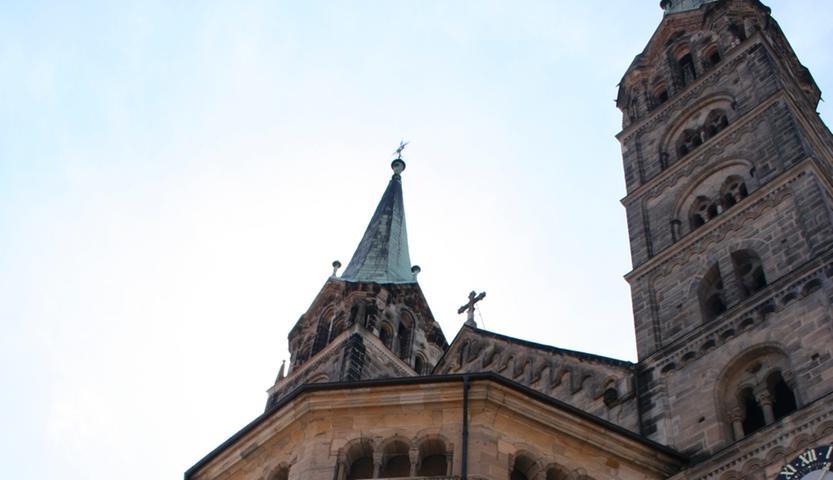 Der romanischeBamberger Dom St. Peter und St. Georggehört zu den deutschen Kaiserdomen und ist mit seinen vier Türmen das beherrschende Bauwerk des Weltkulturerbes Bamberger Altstadt. Er steht auf der markanten Erhebung des Dombergs, der noch weitere historische Gebäude aufweist. Im Inneren befinden sich neben dem Bamberger Reiter das Grab des einzigen heiliggesprochenen Kaiserpaars des Heiligen Römischen Reichs sowie das einzige Papstgrab in Deutschland und nördlich der Alpen. Der Bamberger Dom ist die vierte Basilica minor des Erzbistums Bamberg.
