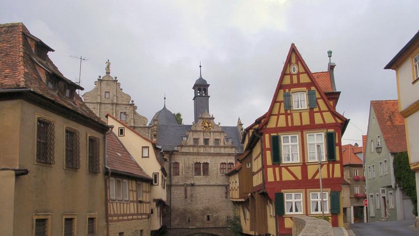 """Es ist ein Fotomotiv, wie man es sich nur wünschen kann: Das romantisch am Breitbach gelegene und ursprünglich auf das 17. Jahrhundert zurückgehende Malerwinkelhaus ist das Wahrzeichen der Stadt Marktbreit. Es hat auch viele Künstler inspiriert - vor allem im Ensemble mit den angrenzenden Gebäuden.Jahrhundertelang diente es als Geschäftshaus. Heute ist in dem malerischen Fachwerkbau dasMuseum Malerwinkelhaus mit den Dauerausstellungen """"Frauen-Zimmer. Lebensstationen in einer fränkischen Kleinstadt"""" und dem """"Römerkabinett"""" untergebracht."""