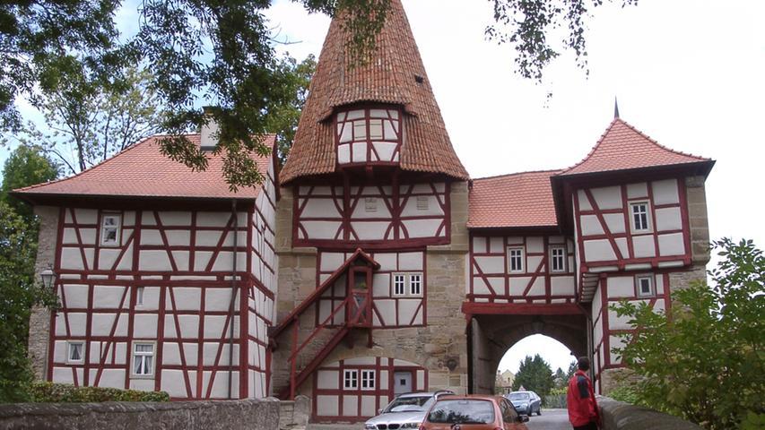 """Das Rödelseer Tor ist das bekannteste und älteste von den drei noch erhaltenen Stadttoren in Iphofen. Mit seinem originellen hohlziegelbedachtem Turm, dem schmucken Fachwerk und dem Torhaus wurde es zum Motiv unzähliger Maler und Fotografen und zugleich zumWahrzeichen der Stadt.Bemerkenswert ist das""""Schlupflöchlein""""in den noch heute eingehängten Torflügeln. Es konntegeöffnet werden, wenn ein verspäteter Ankömmling um Einlass bat."""