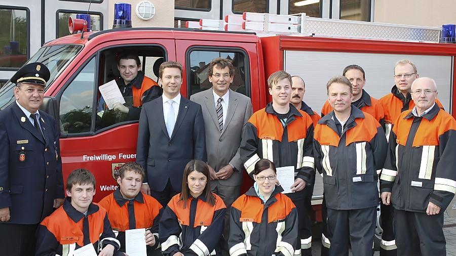 Als einzige Anzugträger im Kreis der Einsatzkräfte händigten Landrat Matthias Dießl (links) und Roßtals Bürgermeister Johannes Völkl (rechts daneben) die neuen Führerscheine an Roßtaler Feuerwehrler aus.