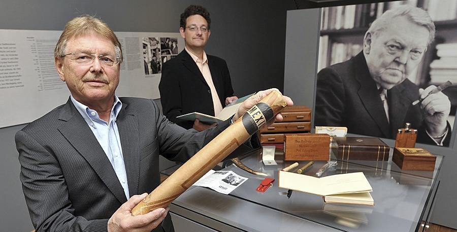 Feuer frei: Olav Bakstad (li.) schenkt Museumsleiter Martin Schramm Gegenstände aus Ludwig Erhards Privatbesitz, die er auf einer Nachlassversteigerung 1997 erstand — darunter eine Zigarre im XXL-Format.