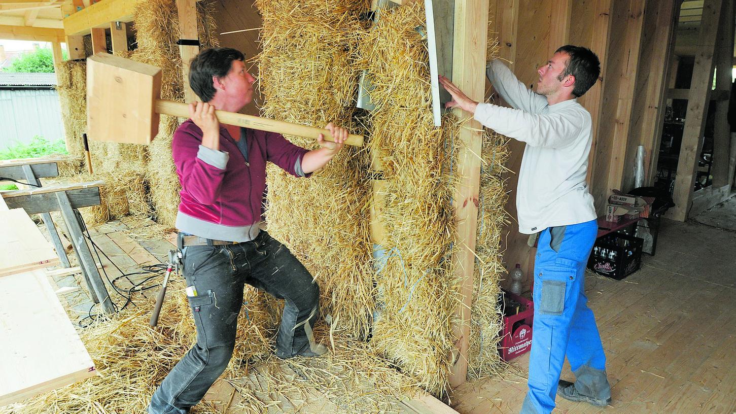 Architektin und Strohbauanleiterin Friederike Fuchs (links) schwingt selbst den Hammer um den Strohballen in das Holzgerüst einzupassen. In Stolzenroth baut sie mit Kollegen an einem Haus aus Stroh.