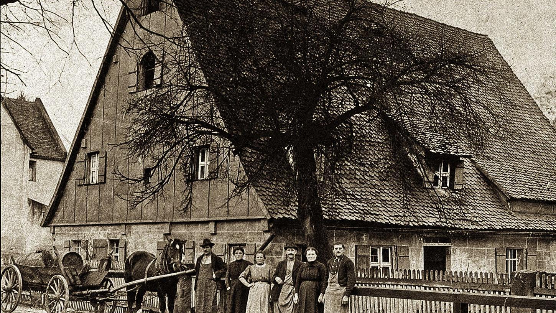 """Die Bleisteinersche Familie ist samt Gesinde vor ihrem Bauernhof in der Erlenstegenstraße 103 angetreten. Die Fotografie aus der Zeit um 1913/14 zeigt eindrucksvoll bäuerliches Selbstbewusstsein, galt """"der Bleisteiner"""" doch neben dem """"Bauern-Kalb"""" als der größte Bauer des Dorfes Erlenstegen. Von links nach rechts: Georg """"Gerch"""" Bleisteiner mit Hut, Kleinmagd Lienhard, Großmagd Fahner, Johann Bleisteiner, Frau Bleisteiner und Georg Bleisteiner."""