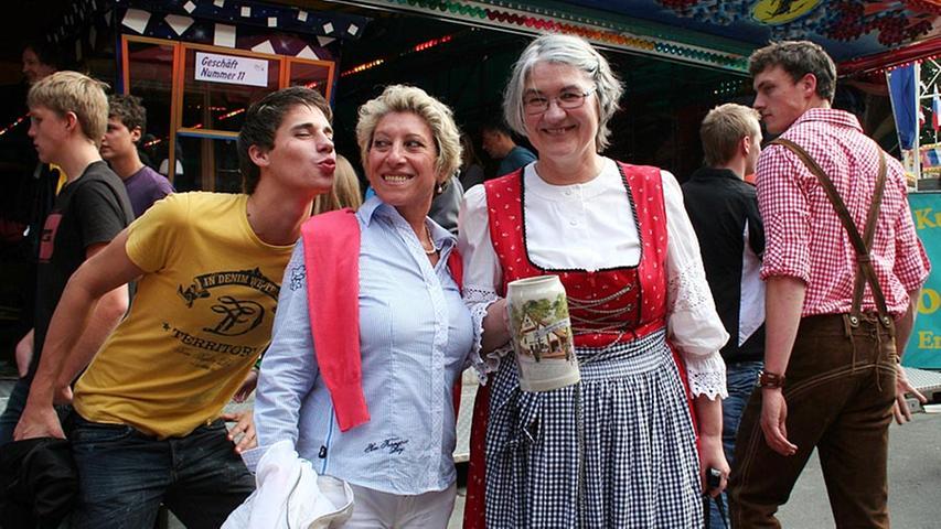 Marye (55) und Hildegard (56), beide aus Erlangen (von links), und ein Unbekannter freuen sich, dass die Bergkirchweih endlich angefangen hat.