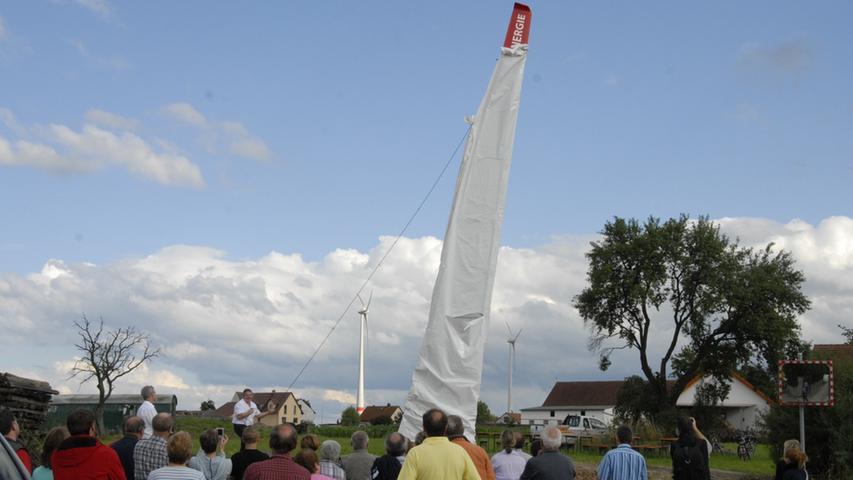 Das Denkmal reckt sich selbstbewusst in den Himmel. Im Hintergrund sind die Windräder der Reuthwind GmbH Co. Kg zu erkennen. An der Bürgerwindanlage sind 108 Bürger beteiligt, die Steuereinnahmen verbleiben so in der Gemeinde Emskirchen.