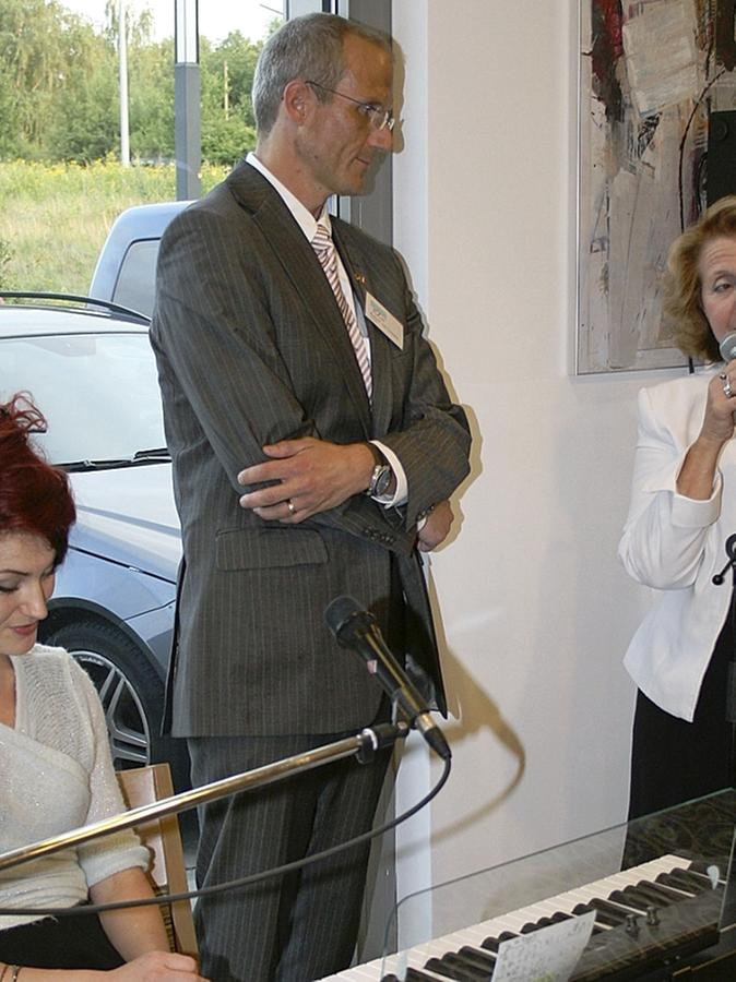 """Am Mikrofon die Sablaiser Komitee-Präsidentin Catherine Gayda, daneben ihr Schwabacher """"Gegenstück"""" Robert van Loosen und die Sängerin und Pianistin Stefanie Stieglmaier, die den Begrüßungsabend musikalisch umrahmte."""