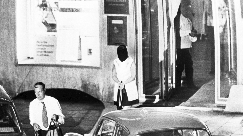 Kurz vor den fatalen Schüssen: Die Geisel Ingrid R. verlässt hinter einem Kassierer die Bank, im Hintergrund die Gangster.