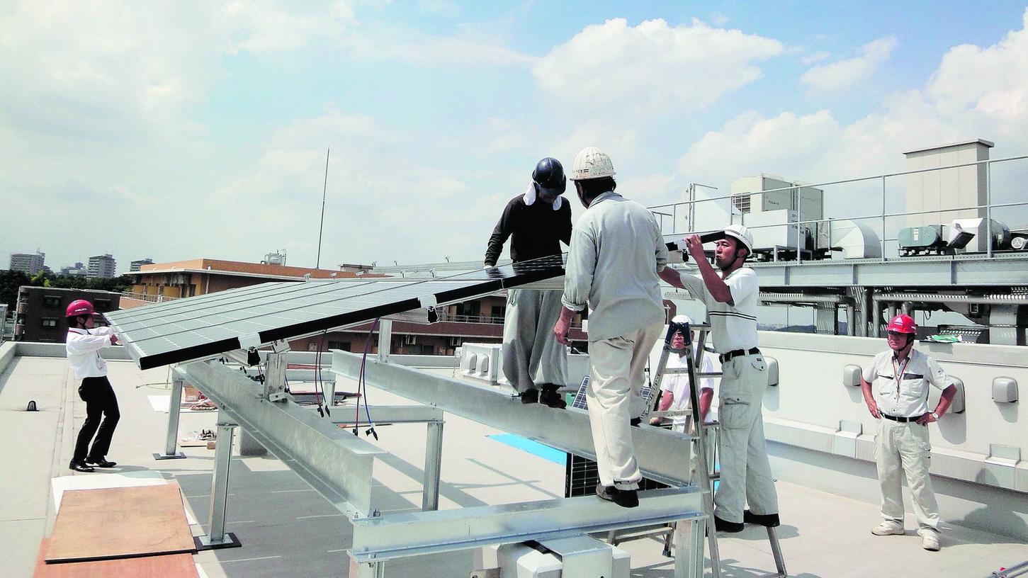 Auf dem Dach der deutschen Schule im japanischen Yokohama montieren Techniker eine 2,4 Kilowatt-Photovoltaik-Anlage. Für die dortige Region ist diese Form der Energiegewinnung noch immer eine Besonderheit.