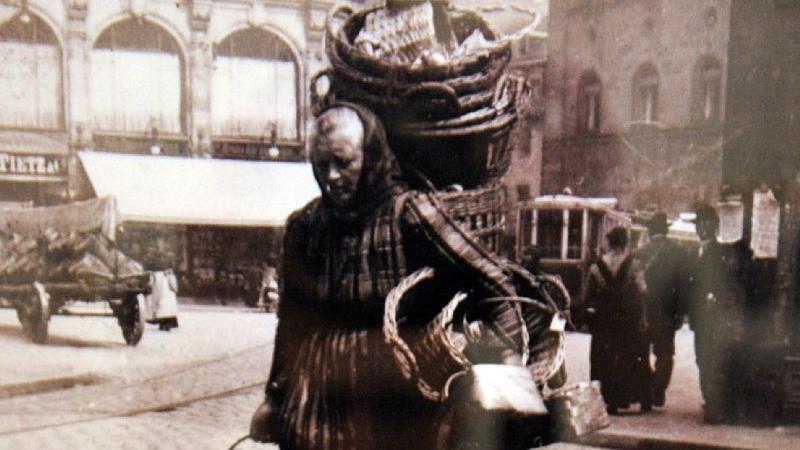 Eine Marktfrau mit leeren Körben am Kohlenmarkt, im Hintergrund das Kaufhaus Tietz, die Südseite des Rathauses und eine Straßenbahn. Nur einen Steinwurf weiter fand man den Obstmarkt.
